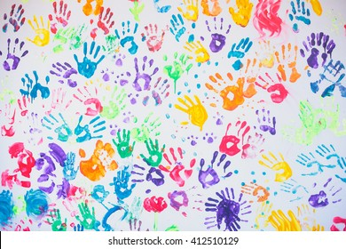 White wall with colorful multicolored hand prints print