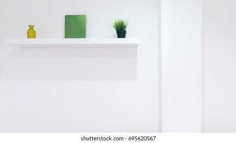 White wall interior with green decoration objects on the shelf