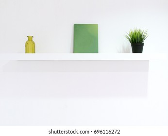White wall interior with green decoration book, and plant pots on the shelf