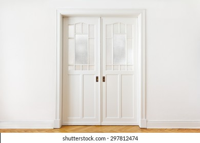 White wall with an old double sliding door with textured glass in an historic building, copy or text space, nostalgic