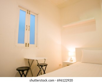 White wall and orange lamp in a warm tone bedroom contrast with blue window frame with white table and black chairs