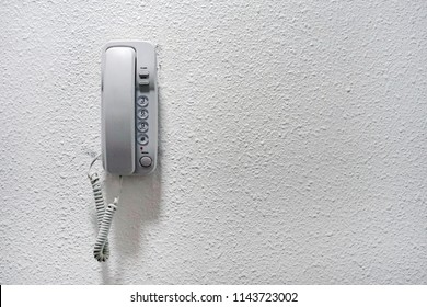 White wall phone. Intercom hung on a white wall. An object of home. White wall mounted contemporary entry phone system. Vintage wall Phone on white background.