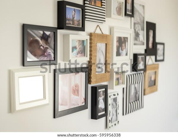 белая стена с фотографиями семьи в различных фоторамках