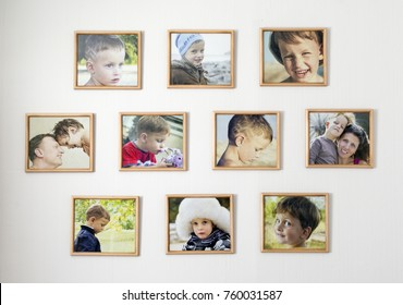 white wall with photos of the family in wooden photo frames