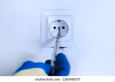 white wall. repair, construction, electricity and home concept - close up of a man in gloves installing new outlet