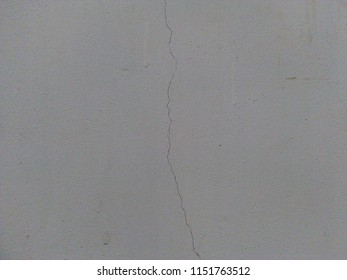 White wall with rift or fracture or fissure or crack or split.