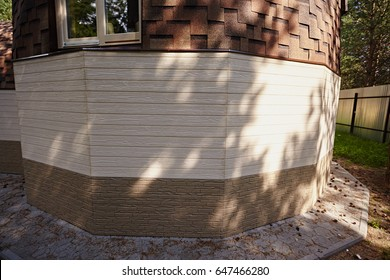 A white wall from the siding of a futuristic domed house. Construction of the domed house. Base and blind area. Three textures. Closeup of a house.