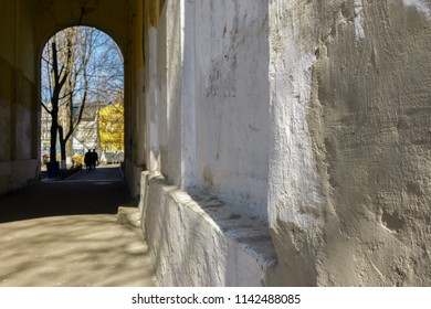 white wall smeared with gray concrete and the arch through which two men walk. walls with painted graffiti, vandalism in the city. Vandals trie to be undetected.
