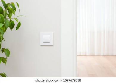 White wall switch on the wall. Light interior