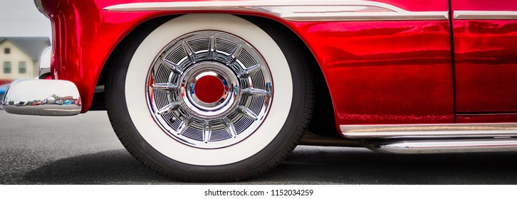The white wall tires and front end of an early fifties classic American car.