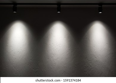 White wall with track light. Spotlight beams on the wall. Dark background.