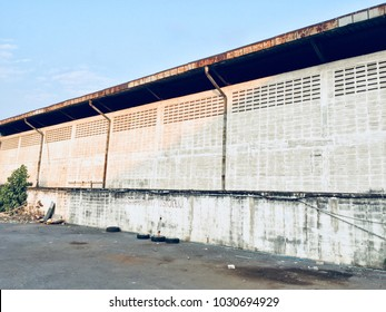 The White wall of warhouse. The back of old and abandoned warehouse.