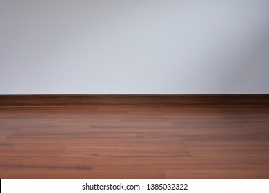 white wall and wood laminate floor in empty room