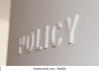 """White wall with the word """"policy"""" embossed, partially blurred"""