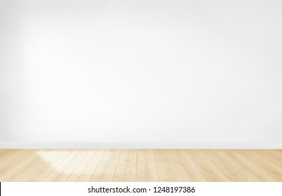 White wallpaper in an empty room with wooden floor