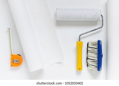 white wallpaper roll with paint roller, brush, tape measure