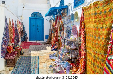 The white walls covered with the colorful rugs for sale and many local souvenirs on each taste, Sidi Bou Said, Tunisia.