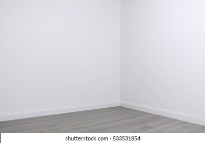 White walls and wooden flooring in the corner of empty room, interior design elements