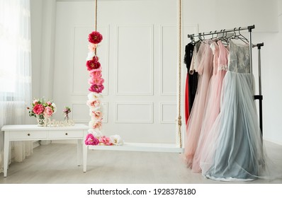 white wardrobe, large white strap, beautiful dresses in pastel colors hang on the hanger. Next to it, a rope entwined with beautiful, intense flowers.