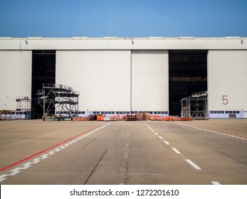 White warehouse number 5 in the airport. Warehouse gate near the runway in airport.