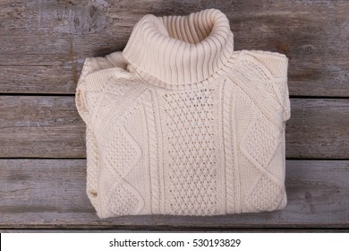 White warm winter sweater. Knitted sweater with a beautiful ornament. Beautifully folded sweater on the old wooden background.