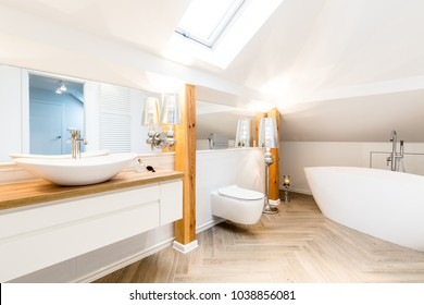 White washbasin in modern bathroom interior with bathtub and toilet on the attic