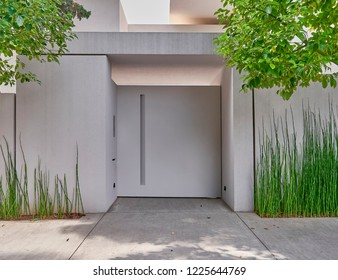 white washed modern house entrance metallic door and bamboo plants
