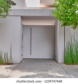 white washed modern house entrance metallic door and bamboo plants, Athens Greece