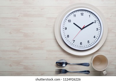 White watch with empty plate on wooden background