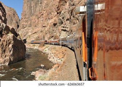 White water river flowing through Colorado's Royal Gorge as a train rounds the bend