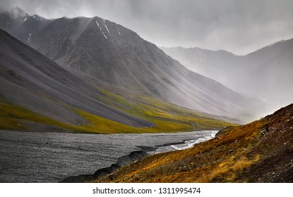 White water river in the mountain valley at overcast cloudy sky in Kyrgyzstan