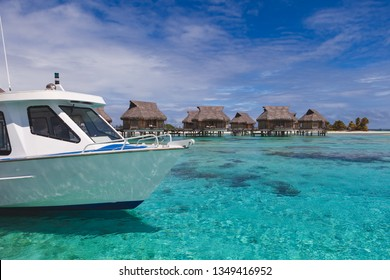 White water taxi boat arrives at tropical island resort paradise in Tahiti next to some overwater bungalows.