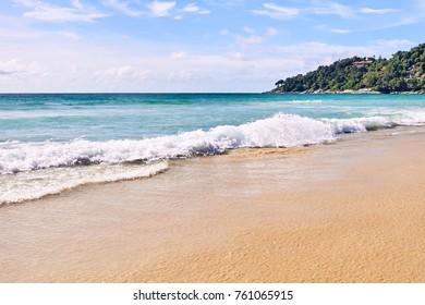 White waves. Blue sea. Clear sky. Green Mountain.