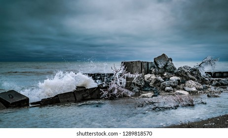 White waves crashing into an icy wall, gloomy dark clouds looming above, and rocks and branches covered in ice, and prickly icicles.