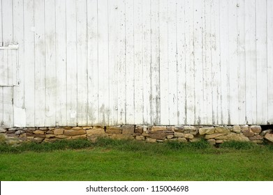 white weathered wall with stone foundation