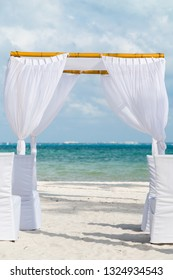 A white wedding alter on a white sand beach in Cancun, Mexico.