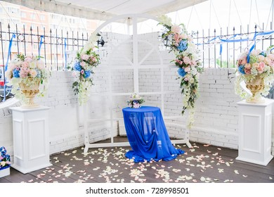 white wedding arch decorated with flowers and cloth