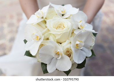 White wedding bouquet of roses and orchids in the hands of the bride