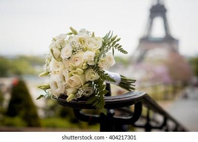 White wedding bouquet under the Eiffel Tower in Paris, France