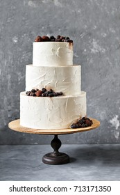 White wedding cake with blackberries, blueberries and chocolate truffles on a grey background, selective focus