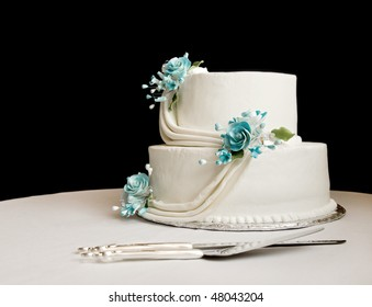 white wedding cake with blue flowers on a table with a black background