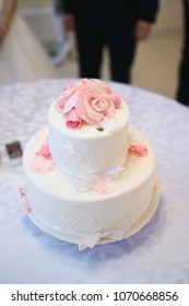 white wedding cake with cream roses on table at restaurant