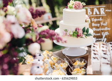 White wedding cake decorated by flowers standing on festive table with lots of snacks on side. Violet flowers on foreground. Wedding. Recetion