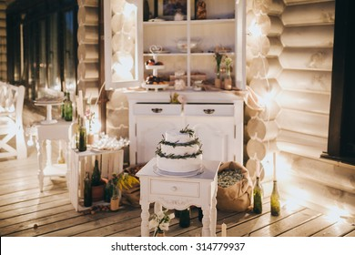a white wedding cake decorated with greenery is on the stand in candy-bar