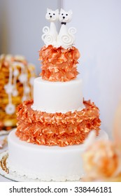 White wedding cake decorated with orange sugar flowers and two sugar kitties on top
