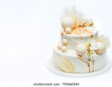 White wedding cake decorated with orchids and chocolate balls