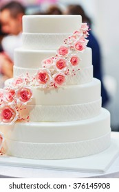 White wedding cake decorated with sugar pink roses