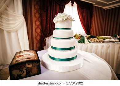 White wedding cake with decorative flower at the top is on the table, along with boxes for gifts