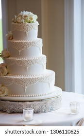 white wedding cake with white flowers and fancy designs on a table