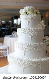 white wedding cake with white flowers and fancy designs with a reception hall in the background